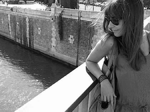 How to be Parisienne is all about going for a natural style of hair and makeup, like this girl, leaning on a bridge over a Paris canal, who's wearing minimal makeup.