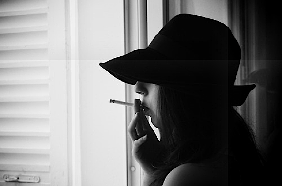It's sad to say, but many Parisiennes smoke cigarettes, like this girl smoking out of a window, and wearing a black hat that covers her eyes.