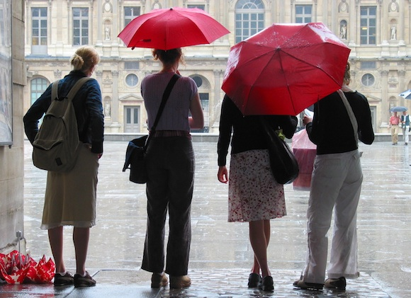 Chic Fashion in the Rain in Paris, means taking your time when you cross the city and seeking shelter so you don't get too wet like these four girls where only two have umbrellas.