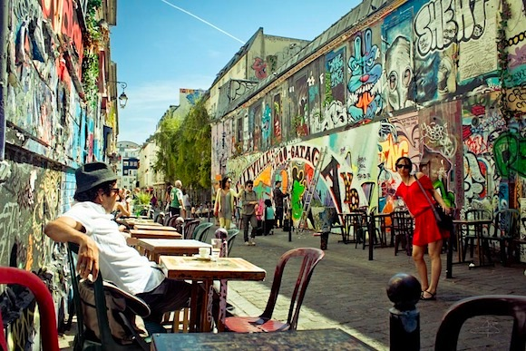 Flirting in France, the art of seduction, is about not being afraid to say hello to people you want to get to know, like this young girl in a red dress waving at a young man who's sat at a bar table outside on graffiti-ridden rue Desnoyez in Belleville, Paris.