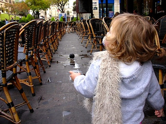 The best Kid-Friendly Dining in Paris, like this empty cafe terrace with this little girl with a dummy in her mouth walking towards a table.