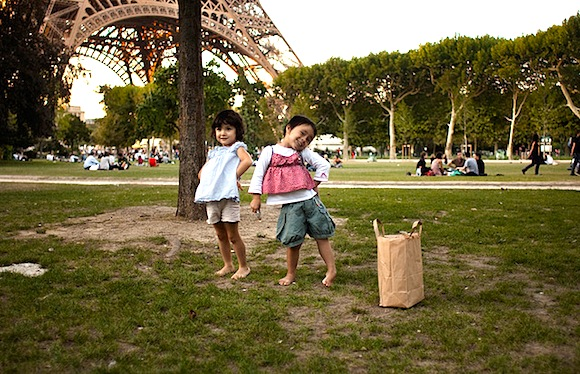 The best Kid-Friendly Dining in Paris doesn't get better than with a picnic at the Eiffel Tower, and these two little girls posing for the camera look like they are having fun.