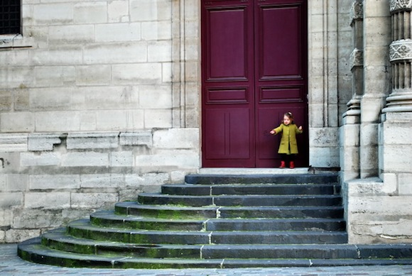 A little girl wearing a yellow coat and standing on the steps of a church in Paris.