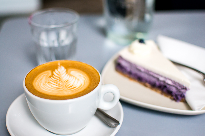 A Cappuccino and a slice of blueberry cheesecake on a table at Paris fashion concept store The Broken Arm's coffee shop in the Marais.