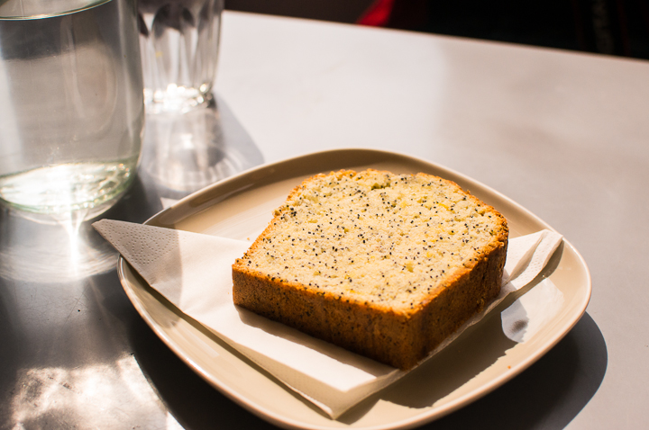 A slice of homemade lemon and poppy seed cake on a white square plate on a table at Paris fashion concept store The Broken Arm's coffee shop in the Marais.