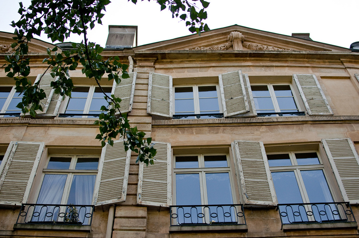 A Paris apartment building with white shutters.