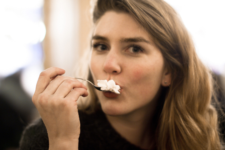 A Newly Single Girl in Paris looking at the camera and eating a spoonful of whipped cream.