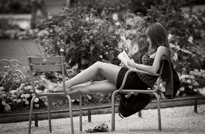 A Newly Single Girl in Paris reads a book in a park in summer.