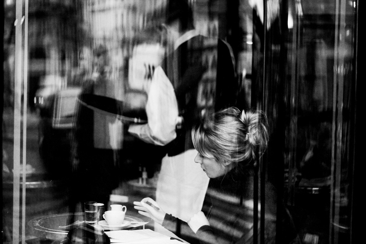 Eating alone in Paris, like this woman sat at a bistro table seen through the window.