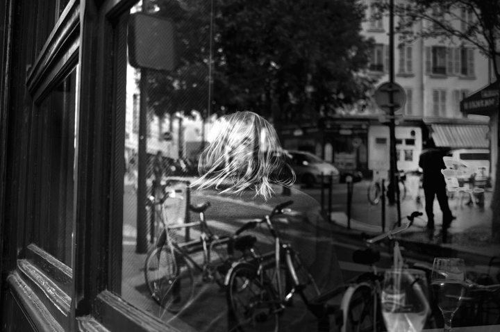 Where to eat alone in Paris, like this blonde woman seen from the back, through a bistro window with reflections of bikes parked nearby.