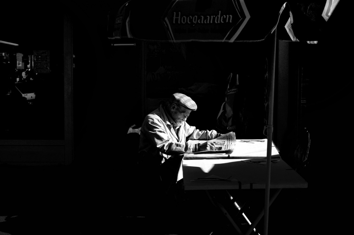 Eating alone in Paris like this elderly man reading the paper flat on a table lit by a spotlight.