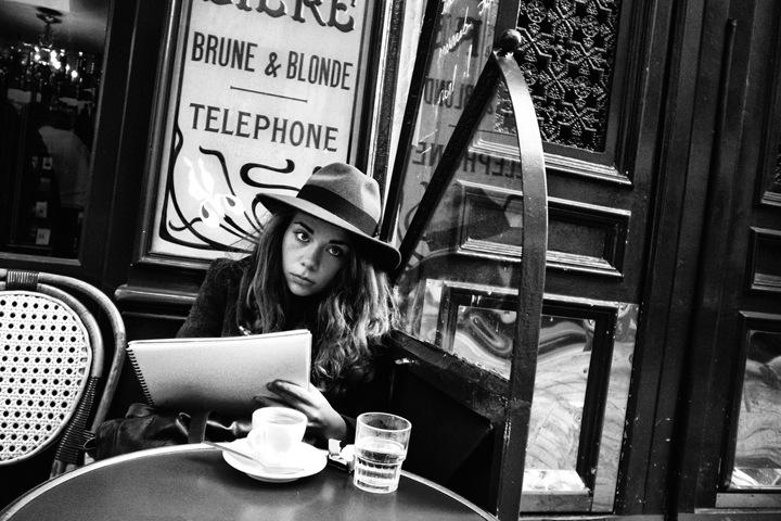 Where to eat alone in Paris, like this woman wearing a hat and sitting outside at a bistro table with her notebook.