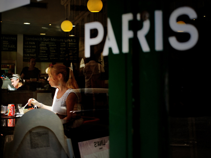 Eating alone in Paris is easy as there are plenty of cozy bistros like this one, with a blonde woman in a white vest, eating a salad, who we can see through the window with the word 'Paris' pasted on it.