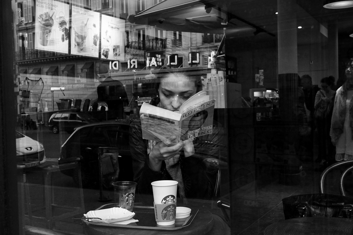 Eating alone in Paris, like this woman at a cafe, reading her book.
