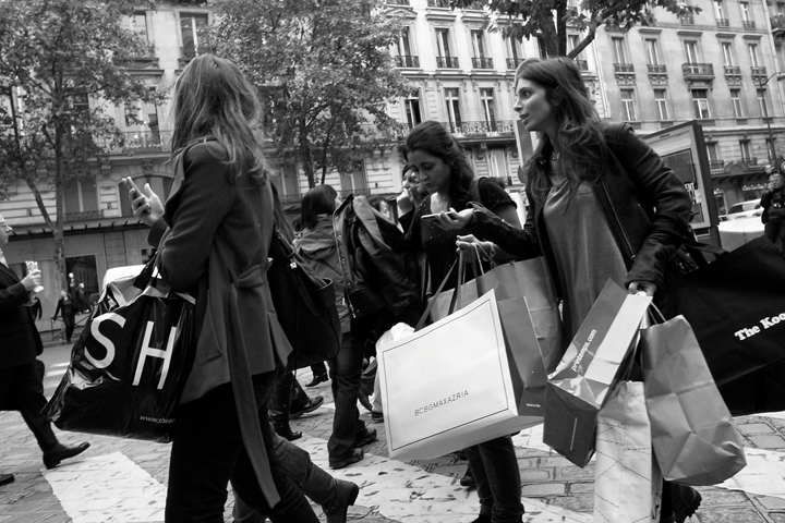 Shopping on a budget in Paris, like these three girls carrying shopping bags as they walk through the streets of Paris.