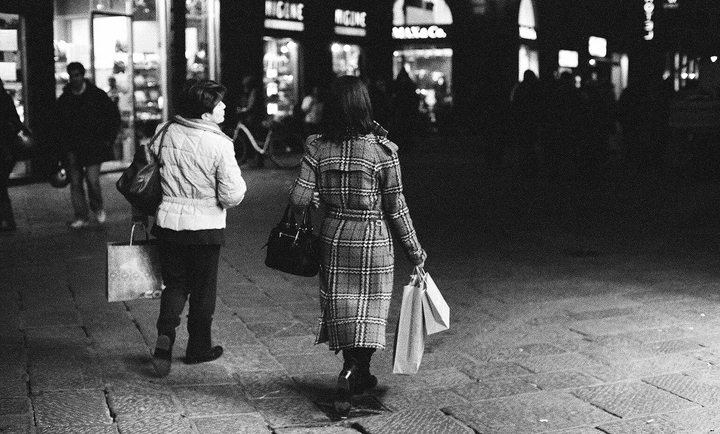Shopping on a budget in Paris is possible when you wait for the sales like these two women walking along a shopping street at nightfall in winter.