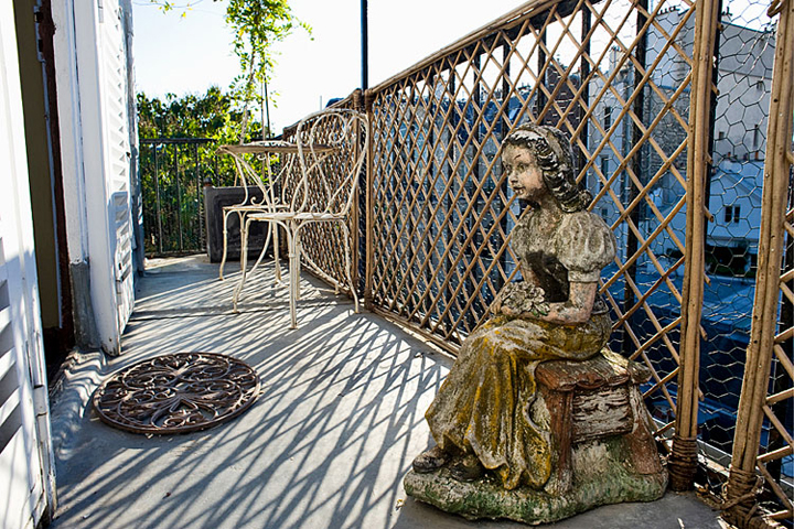 When decorating your Paris apartment, don't forget about the terrace like this one with a table and a chair and a statue of a little girl sitting on a stool.