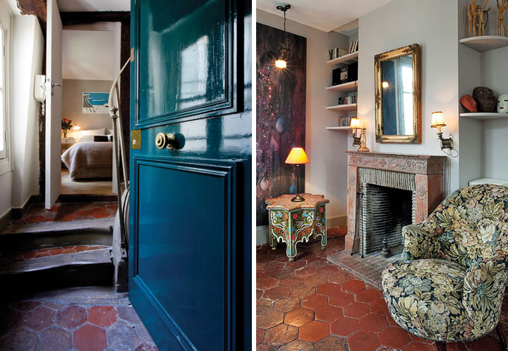 The open blue door to a Paris apartment, with terracotta tiles and warm fabrics in the bedroom (left). The living room with terracotta tiles and a flower-upholstered armchair next to a brick fireplace (right).