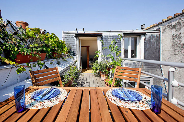 A large, sunny, Paris apartment terrace with a wooden table and chairs and the table set with blue plates and glasses.