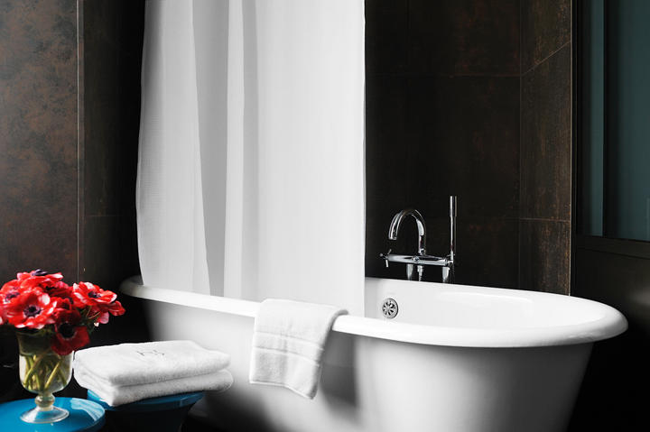 An idea for decorating your bathroom like a Parisian's is to have a free-standing bath tub and fresh flowers for a touch of color.