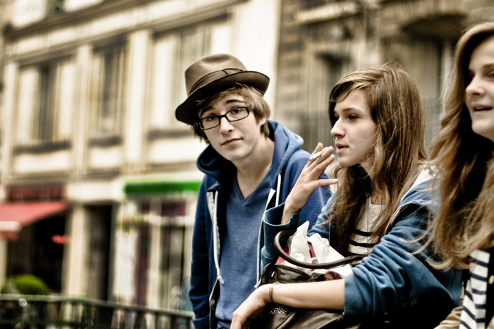 Raising Teens in Paris isn't always easy, especially if they start smoking like this girl with her boyfriend who's wearing a brown hat and glasses.