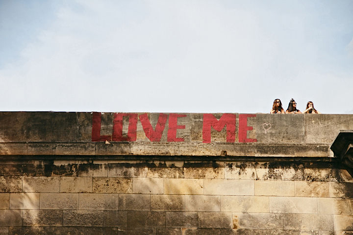 The words 'Love Me' are painted in red on a bridge in Paris where three teenage girls are standing.