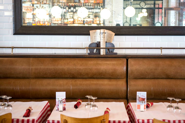 Exploring the Hidden Gems of Paris' Chic 16th Arrondissement like this brasserie with leather seating and white metro tiles.