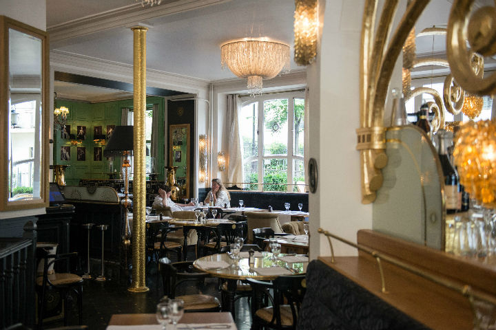 Exploring the Hidden Gems of Paris' Chic 16th Arrondissement like this shiny bistro with gold touches and wooden tables.