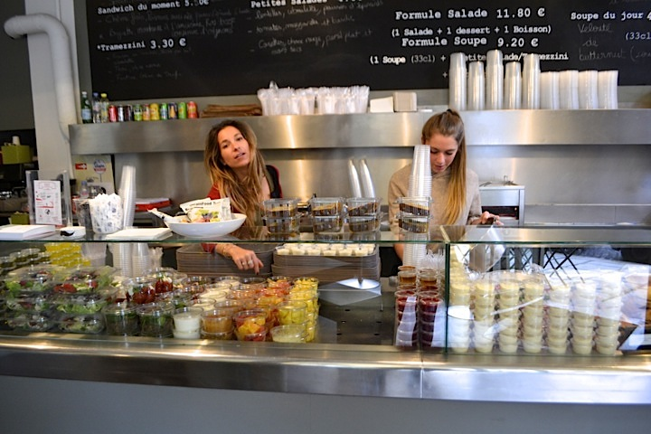 Two women behind the counter packed with salads, at affordable Italian cafe, Il Caffe in Paris' business district.