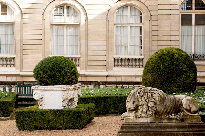 Elegant Eighth, Paris courtyard with a stone lion in a lying down position in the business district.