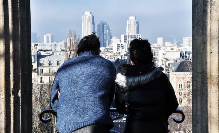 Online Dating in Paris can lead to real-life dating like for this couple at Parc des Buttes Chaumont, with a view of Paris' skyscrapers.