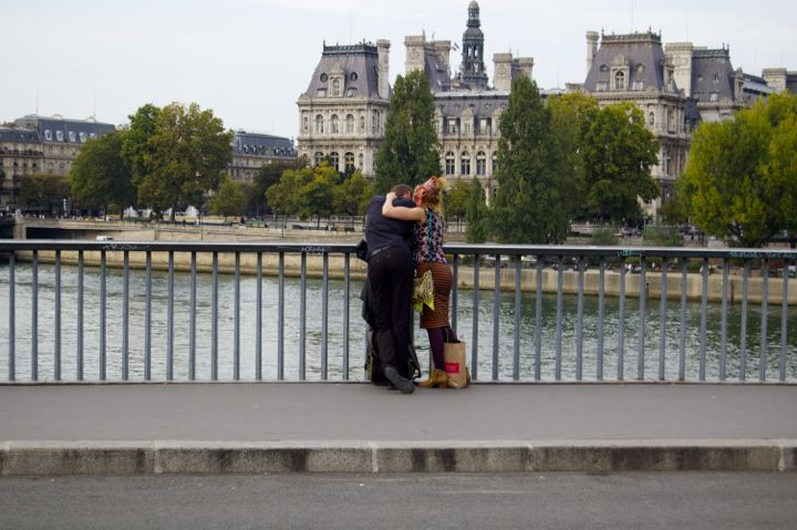Online Dating in Paris can lead to real-life dating like for this couple standing on a bridge straddling the River Seine.