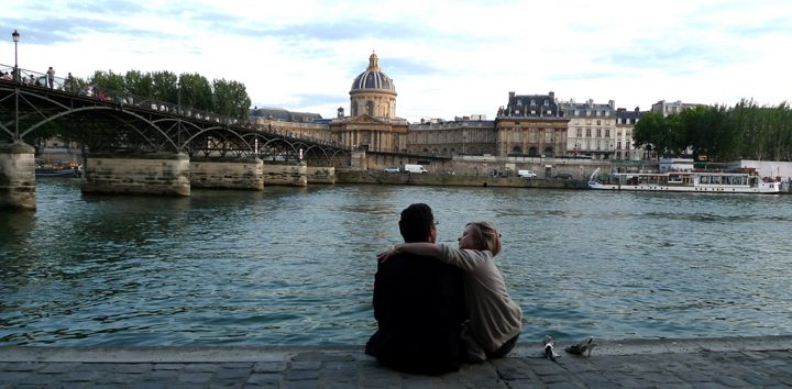 Online Dating in Paris can lead to real-life dating like for this couple sat on the banks of the River Seine.