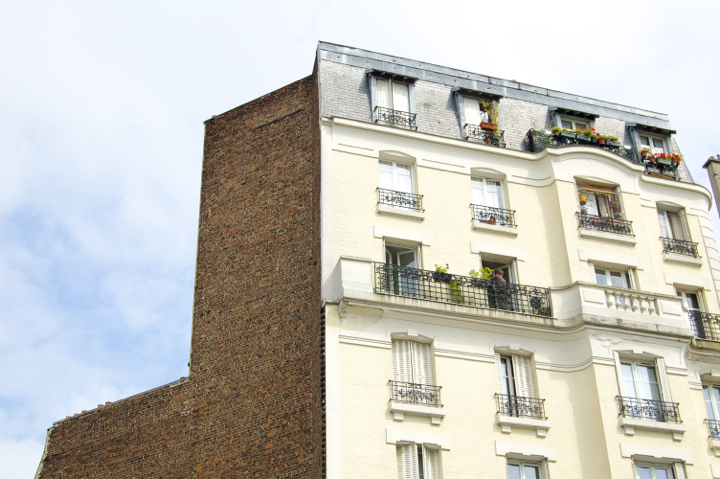 Paris 20th Arrondissement: Best bars, restaurants, and cafés around Belleville and Menilmontant, which have beautiful apartment buildings like this cream one, with shutters and flowers around the windows.