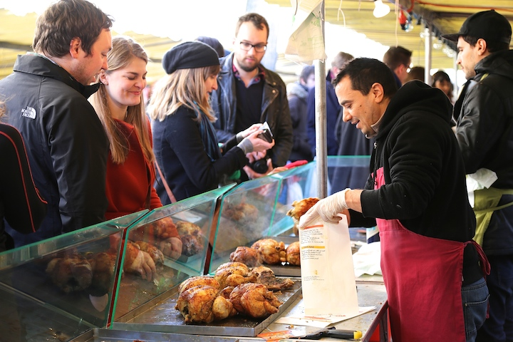 Where to Eat the Best Roast Chicken in Paris: The Chicken Lady at Marché Bastille, where people are queuing in front of the glass counter full of cooked chickens.