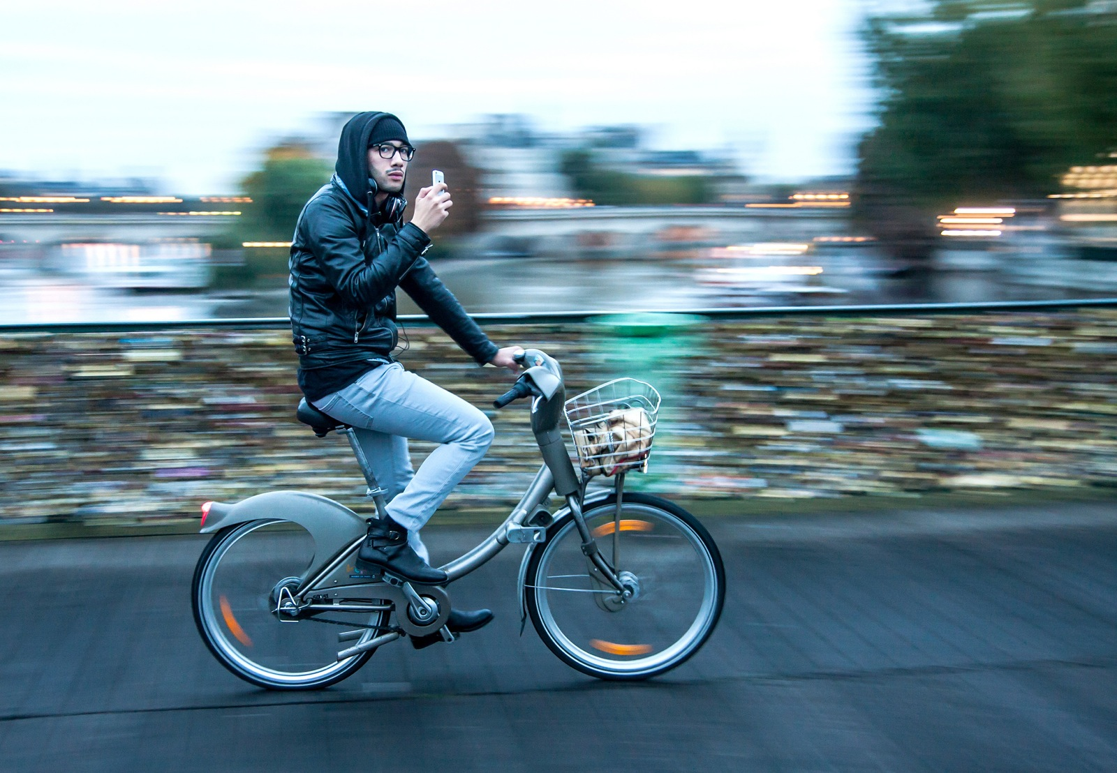 The Five Best Apps for Food-Lovers in Paris will help you find great local places to eat and drink on the road, like this young man on a bike crossing the love lock bridge across the River Seine, who's checking his phone on the way.