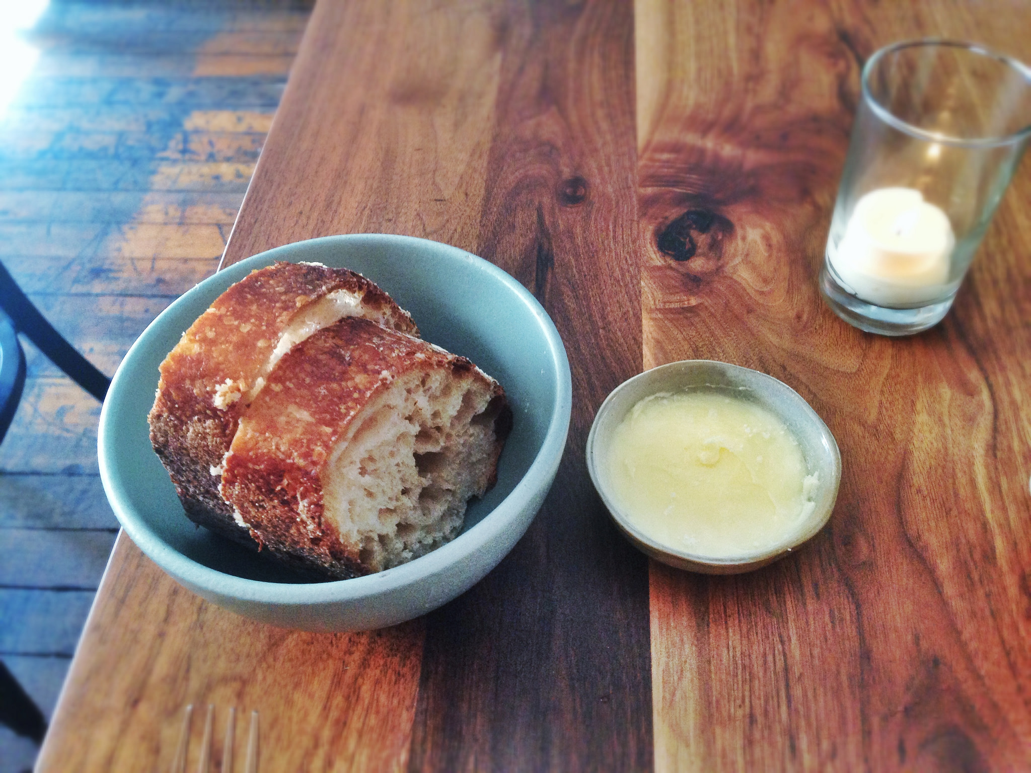 French butter just with a good artisanal baguette tastes incredible, like on these two slices of baguette in a blue bowl next to a dish of butter on a wooden table.
