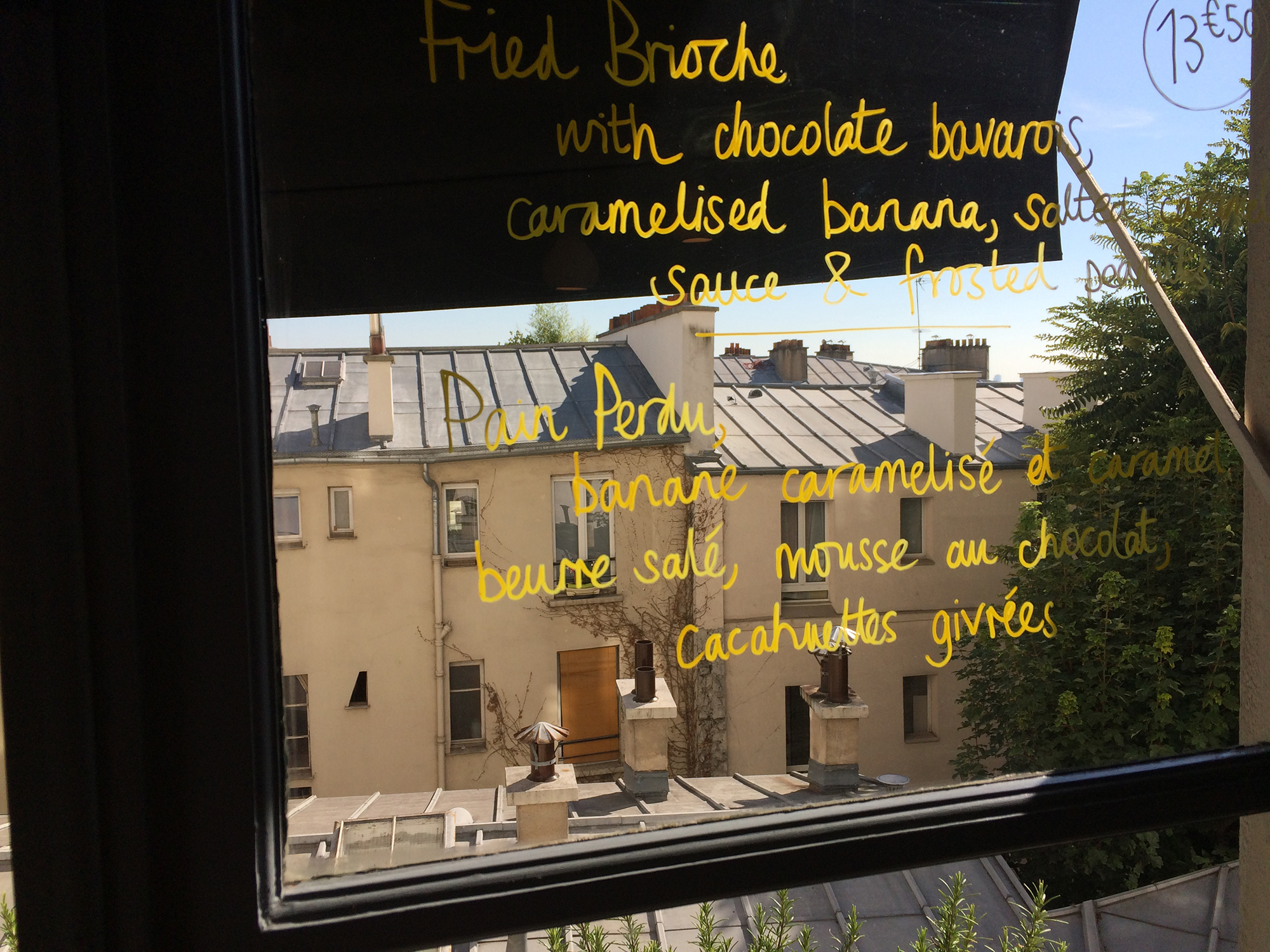 The handwritten menu on the window of go-to Paris coffee shop Hardware Sociéte in Montmartre. You can see the apartment buildings with zinc rooftops reflected in the window.