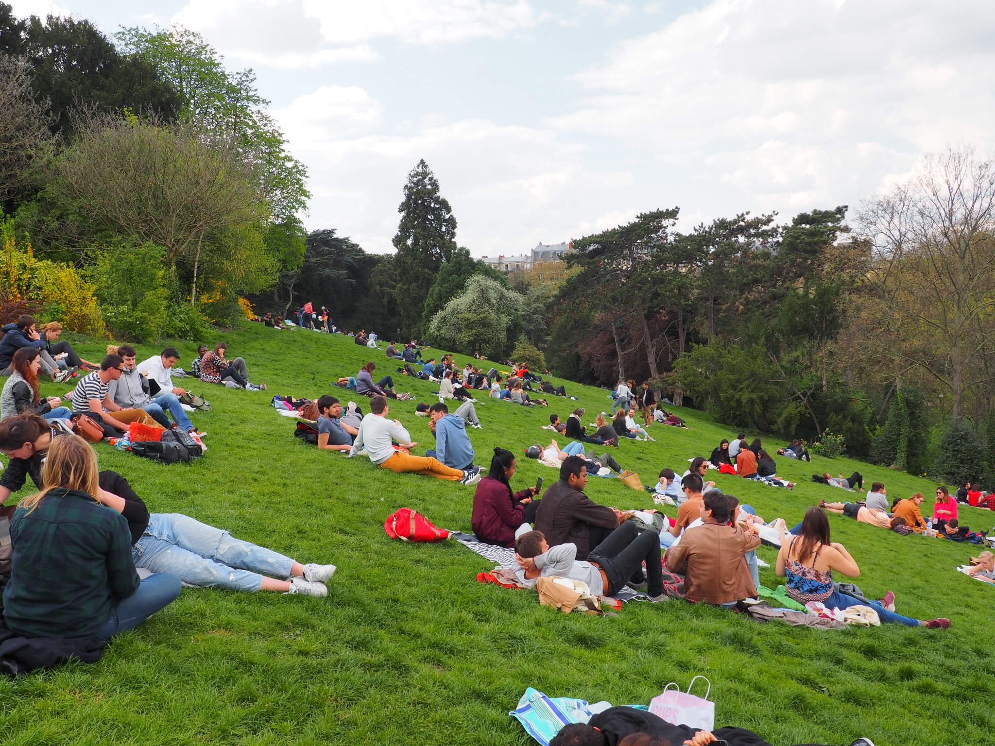 Our guide to spending Sundays like a local in Paris includes tanning in a park, like these Parisians.