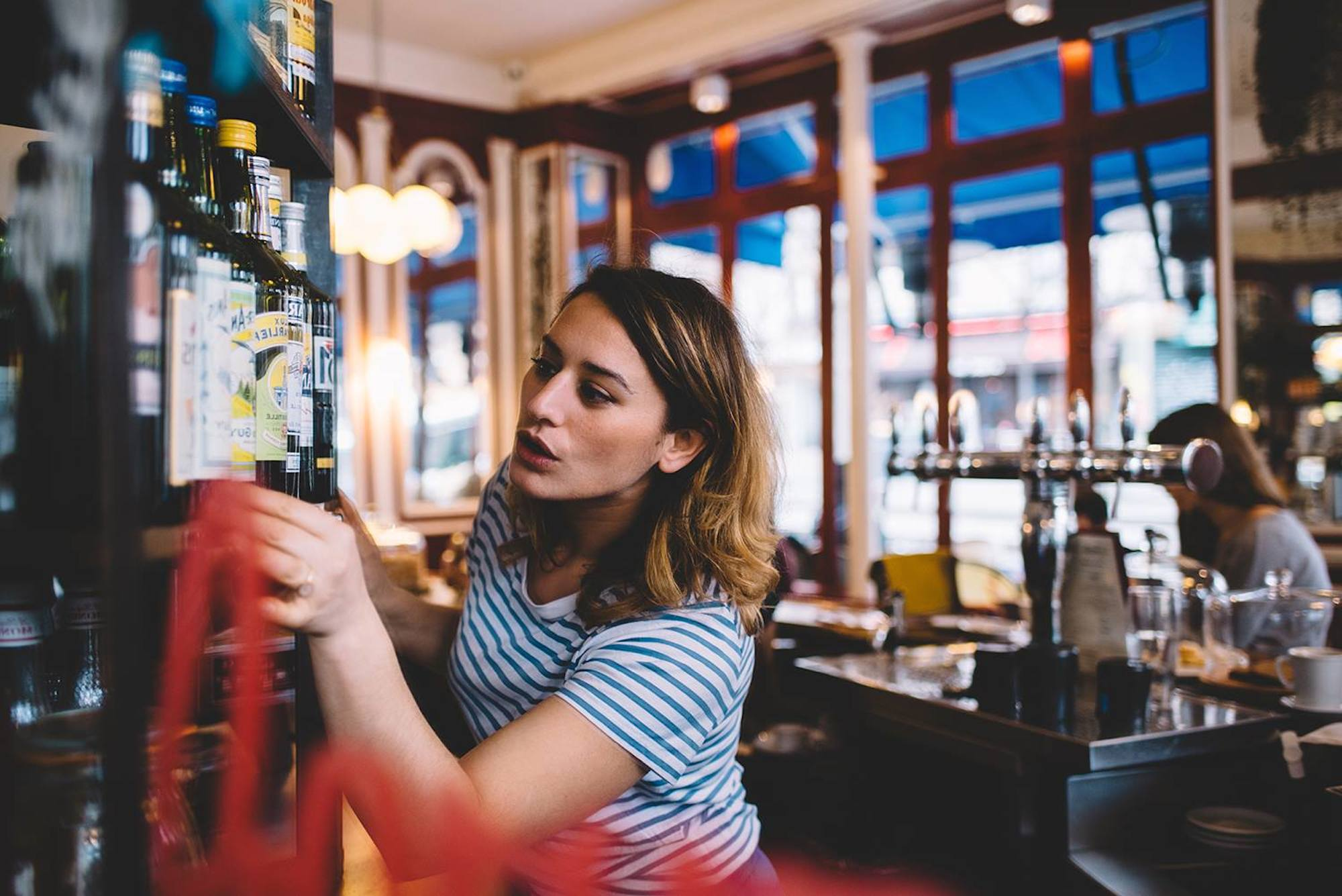 A waitress looking for a bottle on a shelf behind the bar at La Fontaine de Belleville, a top brunch spot in Paris.