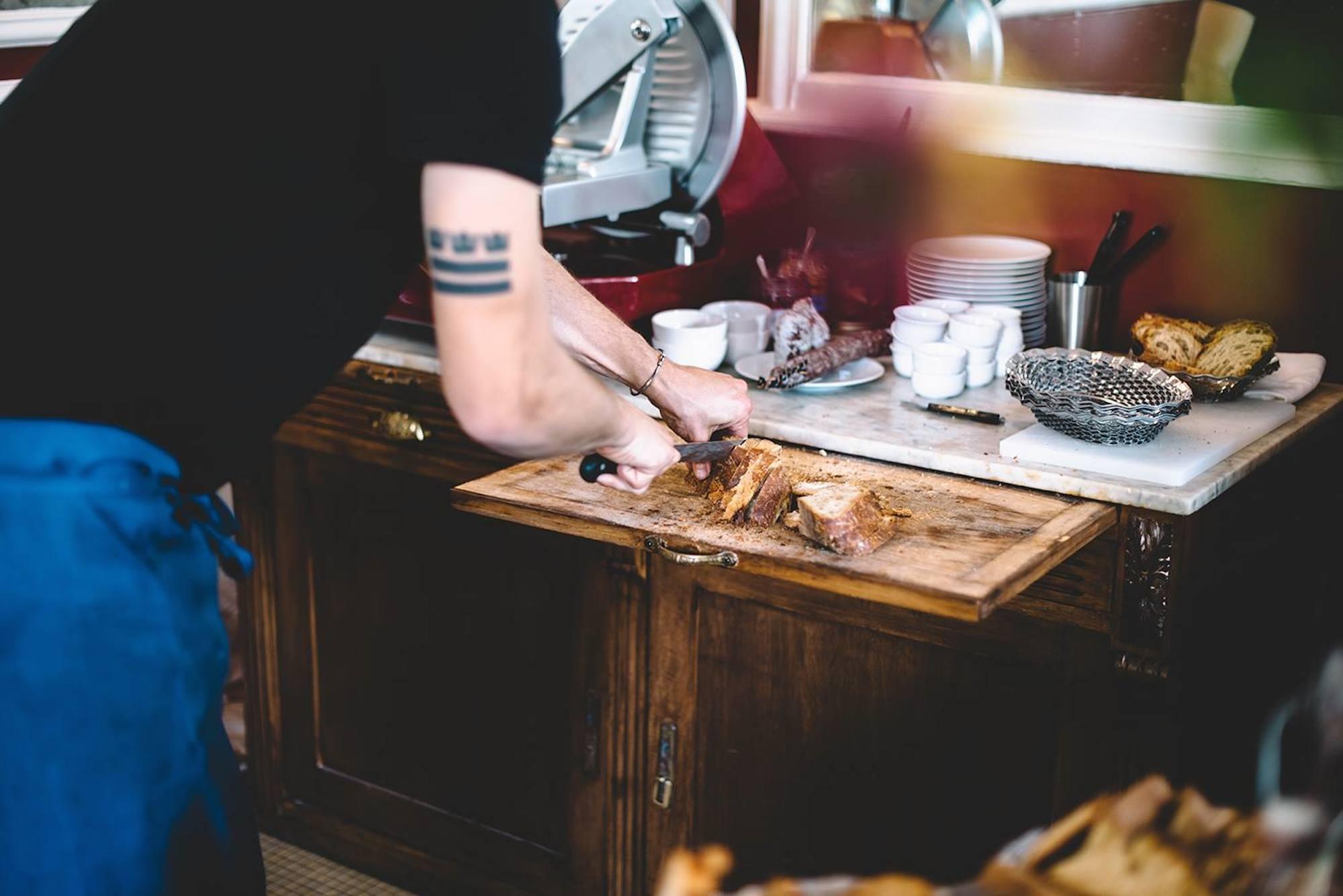 A waiter slicing baguettes at La Fontaine de Belleville, a top brunch spot in Paris.