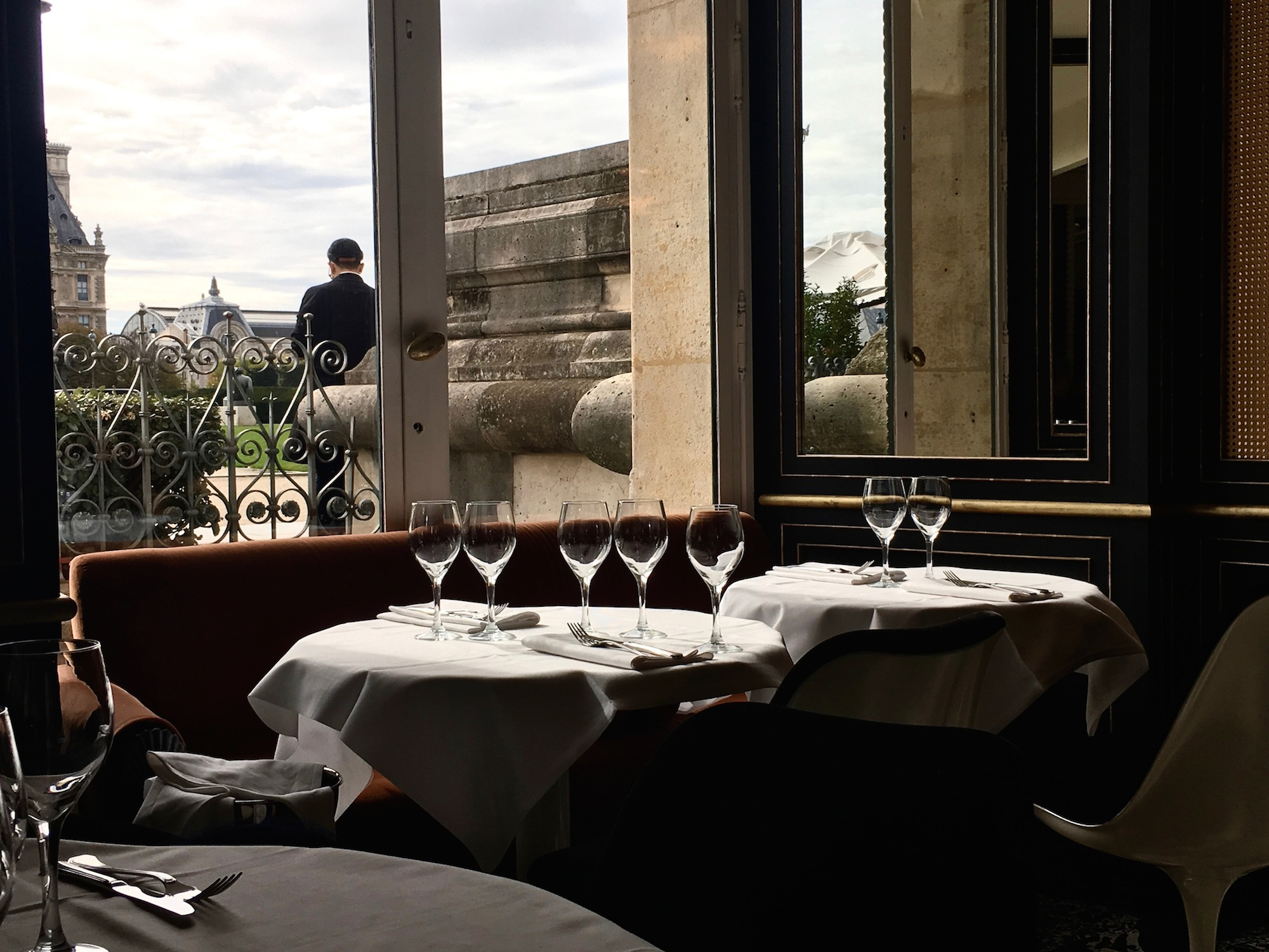 A table at Loulou restaurant in Paris, with a view of the nearby square out of the window.