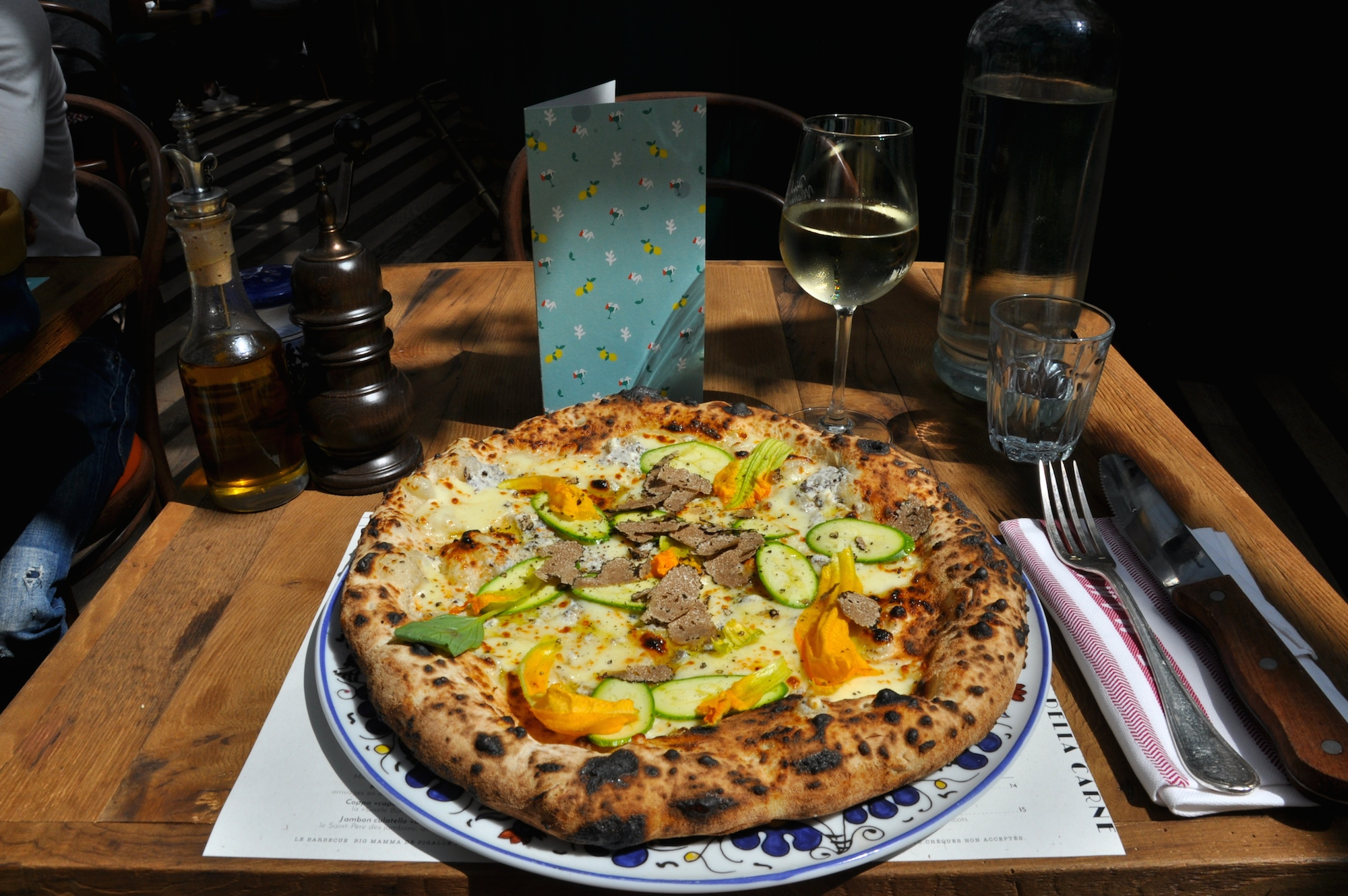 The Big Mamma Group offers Trendy, Fresh, Authentic Italian Dining in Paris, including stone-baked pizzas with veggie and truffle toppings like this one, set on a wooden table besides a glass of white wine.