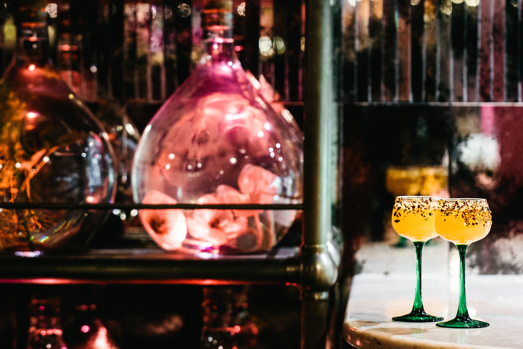 The Big Mamma Group offers Trendy, Fresh, Authentic Italian Dining in Paris as well as creative cocktails with fermented fruit in big rounded glass vats, like in the two glasses on the counter with green stems.
