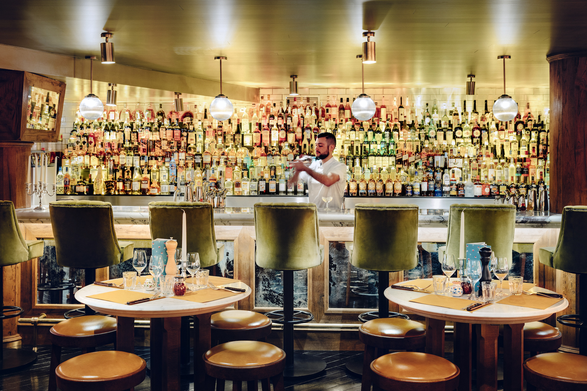 The Big Mamma Group offers Trendy, Fresh, Authentic Italian Dining in Paris, as well as cocktails like at this location's bar with an array of spirits where a mixologist is shaking a cocktail.