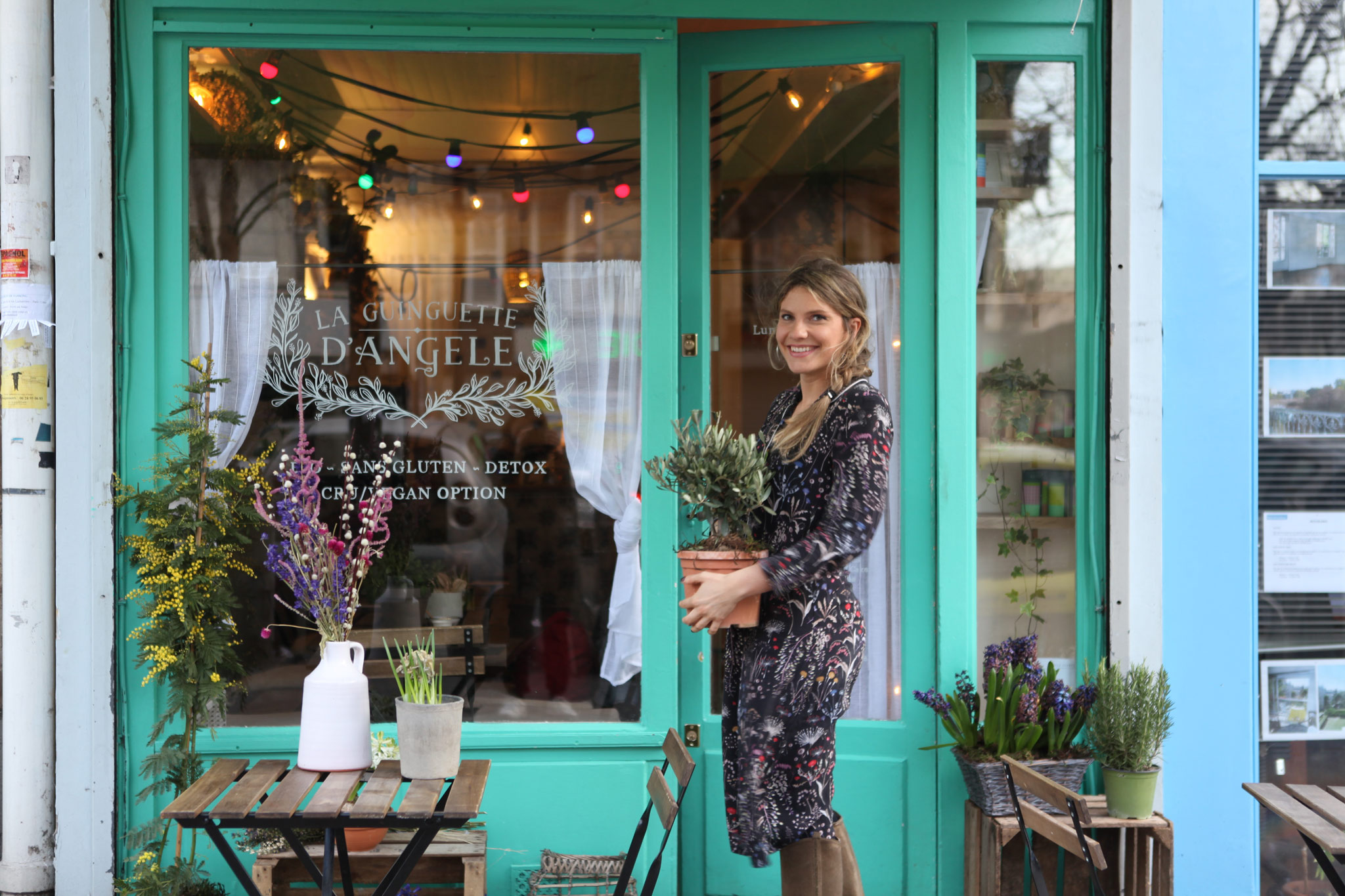 One of the best gluten-free restaurants and bakeries in Paris is la Guiguette d'Angèle, with its bucolic decor of fresh flowers, and Angèle's smile, who you can see here as she carries a small potted olive tree to the terrace outside the restaurant.