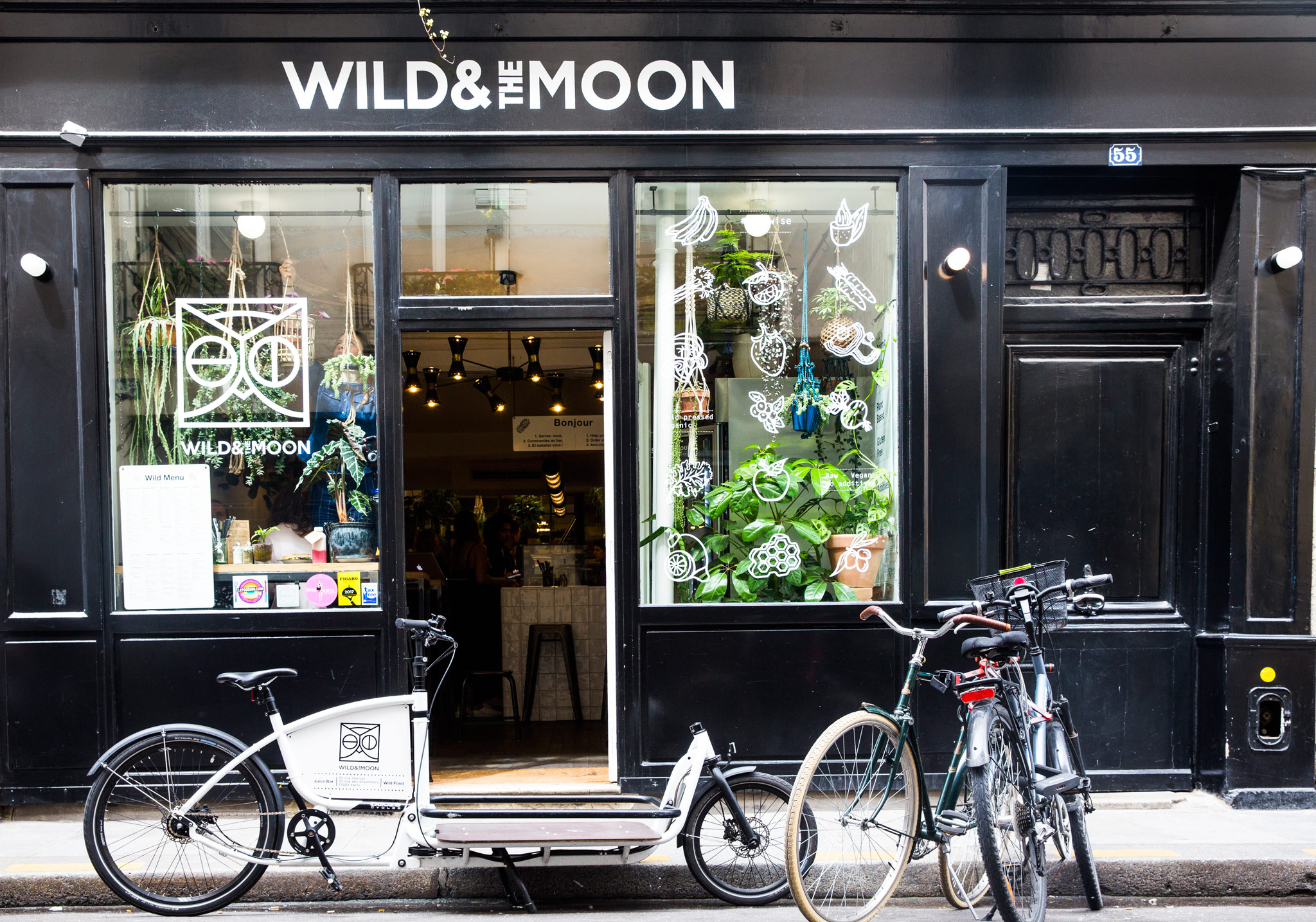 One of the best gluten-free restaurants and bakeries in Paris is Wild and the Moon, whose exterior you can see here, with bikes parked outside its black shop front.