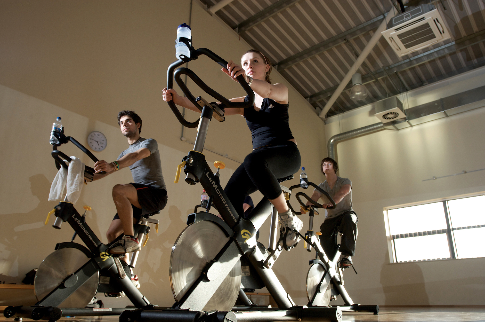 Where to exercise in Paris, and do indoor cycling, like these three people on indoor bikes.