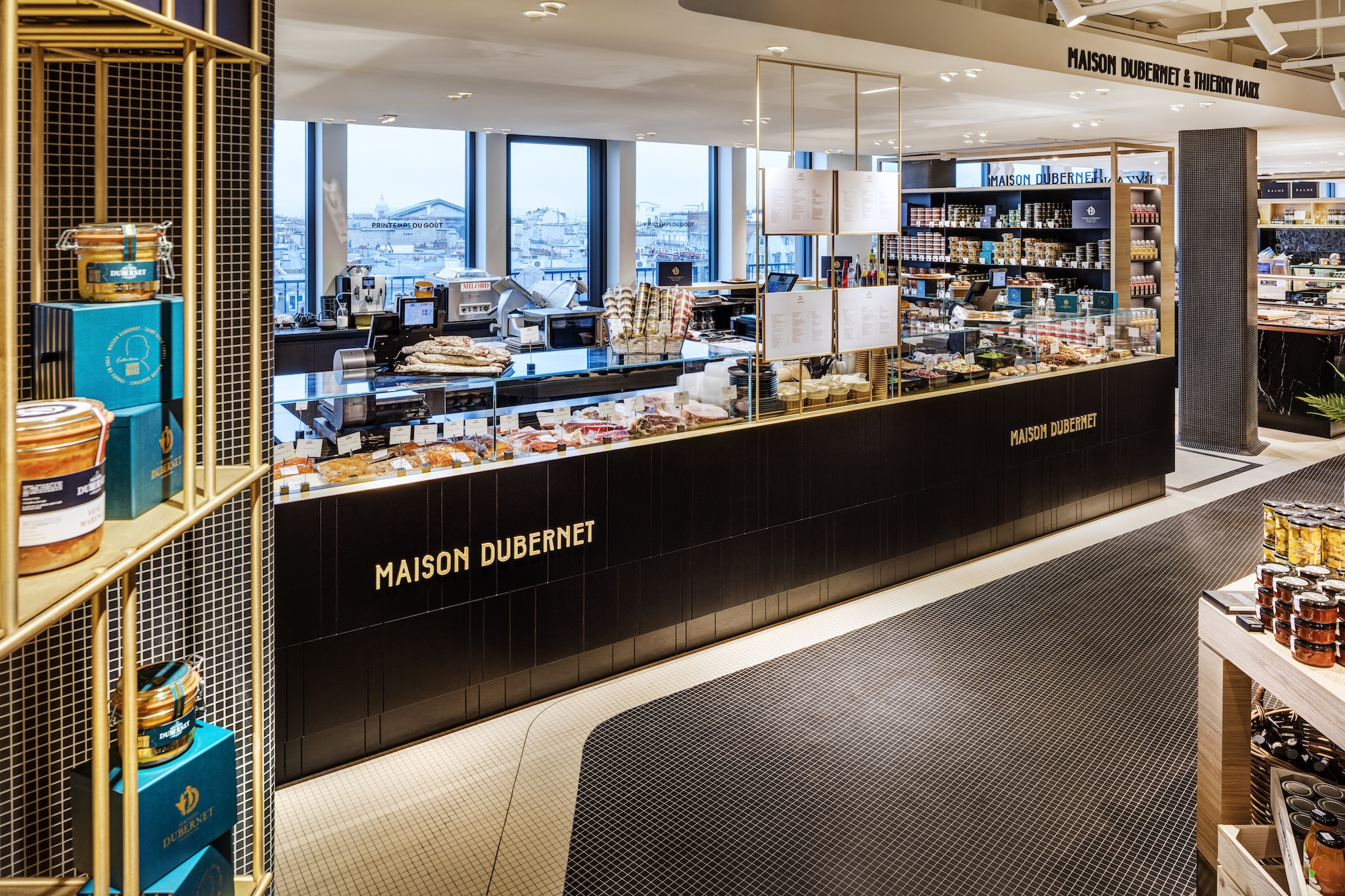 Luxury food mall Printemps du Gout counters in Paris with views of the Eiffel Tower.