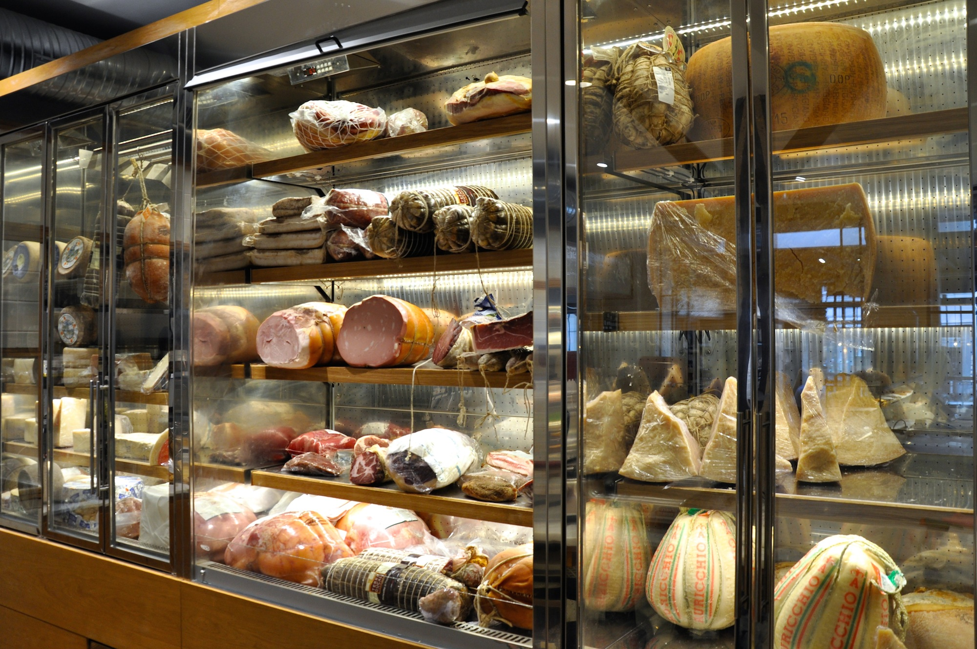 Hams and cheeses in fridges at Roberta Italian restaurant in Paris' Montmartre area.